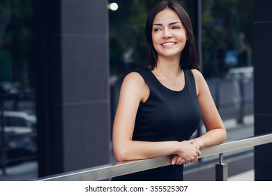 Pretty smile woman with her arms on parapet