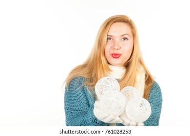 Pretty smiling adult woman dressed in warm sweater, gloves and scarf with holding a Christmas toys on hands. New Year celebration concept. Studio shoot isolated on abstract blurred white background