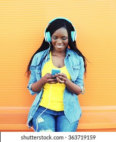Pretty smiling african woman with headphones listens to music over orange background