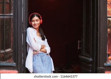Pretty smiling asian girl in white shirt happily closing eyes leaning on vintage door listening music in red headphones outdoors