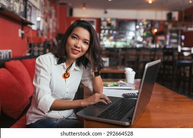 Pretty smiling bar owner working on laptop at the table