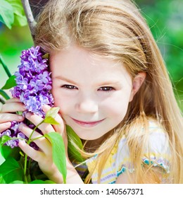 Pretty smiling blond little girl with flowers of blooming lilac in her hands