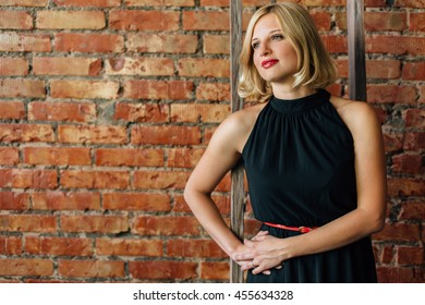9804d441d8 pretty smiling blonde woman with red lipstick in black dress posing behind  the stairs in front