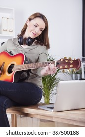 Pretty smiling brown haired girl sitting on desk playing some records on guitar while using laptop for support