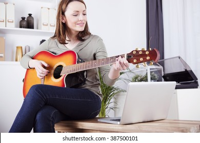Pretty smiling brown hairs girl casual dressed sitting on a desk playing records on guitar supported by laptop