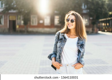 Pretty smiling brunette girl walking on the street