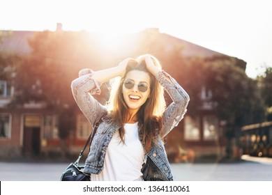 Pretty smiling brunette girl walking on the street