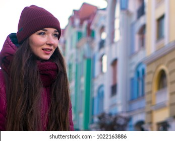 Pretty Smiling Brunette Girl Wearing Purple Winter Coat, Hat and Scarf, Walking by European Street at Winter