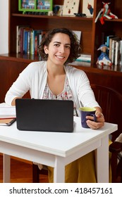 Pretty smiling brunette woman working on laptop with notebook and cup of tea at home. Selective focus
