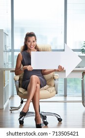 Pretty smiling business woman holding big white paper arrow