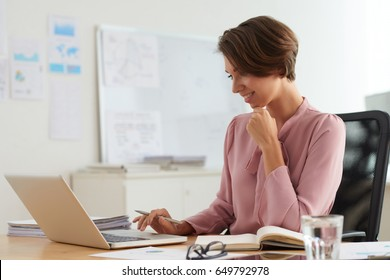 Pretty smiling business woman working on laptop at tablet