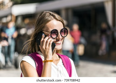 Pretty smiling caucasian tourist girl in stylish sunglasses is talking on the phone happily in the old city center, sunny day