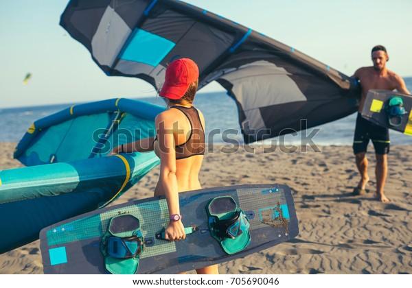 Ziemlich lächelnd kaukasische Frauen und männlicher Kitesurfer, die mit ihrem Drachen am Strand spazieren