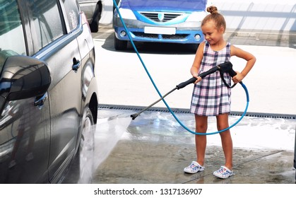 Pretty smiling cute little preschool girl in summer dress helping to parents use coin-operated self-serve car wash, clean auto wheels tires exterior holding high-pressure sprayer standing outdoors