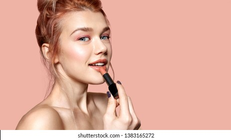 Pretty smiling female applying lipstick. Woman posing in studio with bare shoulders. Copy space on right side. Beauty and cosmetics concept. Isolated on pink