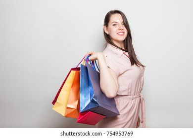 Pretty smiling female and color shopping present bags