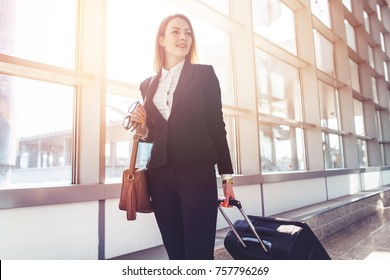 Pretty smiling female flight attendant carrying baggage going to airplane in the airport