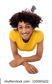 Pretty smiling female model with curly hair relaxing on the floor.