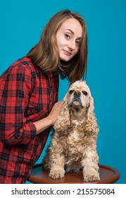 Pretty smiling girl with american spaniel on a blue background