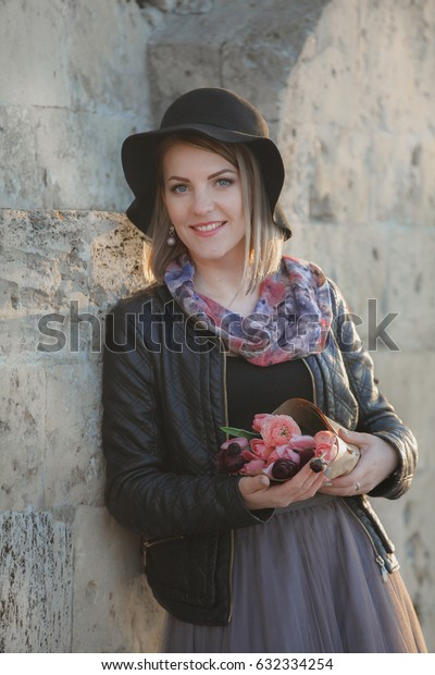 Pretty smiling  girl in black hat with tulips