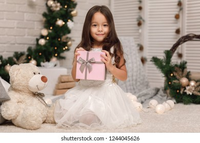 Pretty smiling girl holding Christmas gift in hand at home