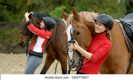 Pretty smiling girl huggings her horse at ranch. Young farmer woman preparing her horse for training at farm. People, animals, lifestyle.