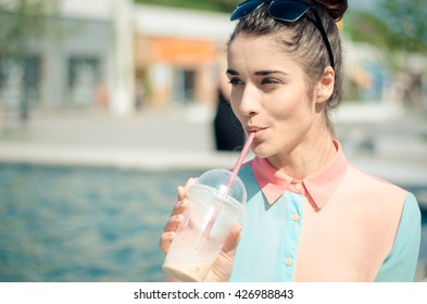 pretty smiling girl with iced latte in sunny city