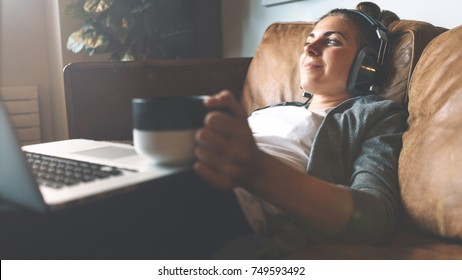 Pretty smiling girl listening to music from headphones with pleasure at coworking office, lying on sofa, using laptop, drinking hot coffee from nice cup and resting.