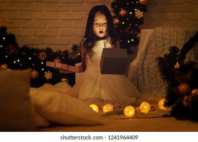 Pretty smiling girl opening magical box with Christmas gift at home