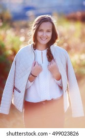 Pretty smiling girl in sunlight. Colorful autumn park. Vertical shoot
