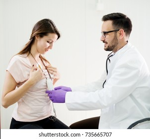 Pretty smiling girl wearing Holter monitor device while doctor checking her health condition.