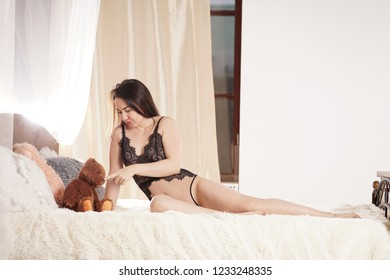 pretty smiling happy woman wearing lace lingerie and relaxing on the white bed with her brown teddy bear toy alone in her bedroom at home