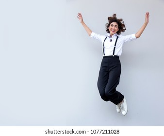 Pretty smiling joyfully asian female with curly short hair jumping action on white background, dressed hipster, being happy. Studio shot of good-looking beautiful woman and copy space.