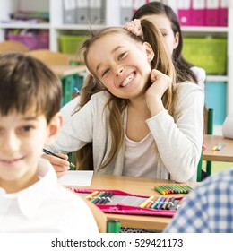 Pretty smiling little girl sitting in a classroom with friends during lesson