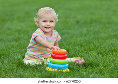 A pretty smiling little girl sitting on the green grass is playing with a toy pyramid