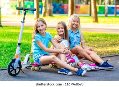 Pretty smiling little girls sitting near grass in sunshine evening park with kick scooters and roller skates