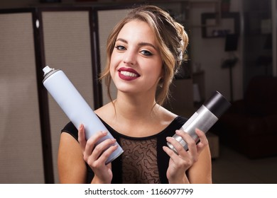pretty smiling model with perfect makeup and coiffure holding two hair sprays and exploring them. concept of professional hairdresser products