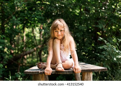 Pretty smiling pensive girl sitting on the old bridge in the forest