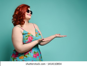 Pretty smiling plus-size fat woman in fashion sunglasses and colorful sundress stands in profile with her head slightly bowed and demonstrates someting on her open palms on mint background