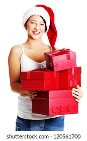 Pretty smiling teen caucasian girl in Santa`s hat holding gifts. Isolated on white.