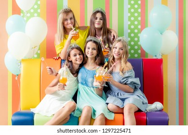 Pretty smiling teenage girls in dresses and crowns sit hugging together on the colorful sofa with baloons at birthday party on the striped colorful background