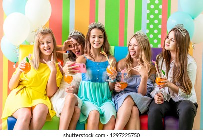 Pretty smiling teenage girls in dresses and crowns sit hugging together holding beverages and taking selfie at birthday party on the striped colorful background
