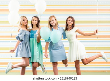 Pretty Smiling Teenage Girls In Dresses Standing Together With Ballons At Birthday Party On The Striped