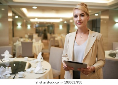 Pretty smiling wedding planner with tablet computer in restaurant