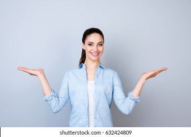Pretty smiling woman in blue shirt isolated on gray background asking you to make a choice between two products