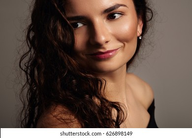 pretty smiling woman with cyrly hair closeup portrait in studio