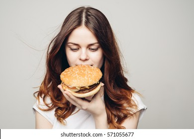 Pretty smiling woman eating a burger.