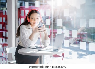 Pretty smiling woman listening to music from headphones with pleasure at coworking office, sitting and using laptop, drinking hot coffee from nice cup and resting.