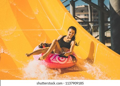 pretty smiling woman on the rubber ring having fun on the orange water slide in the aqua park. Summer Vacation. Weekend on resort