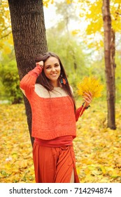 Pretty smiling woman portrait, walking in autumn park, dressed in casual orange sweater and skirt, autumn outdoor